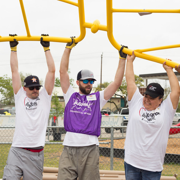 Volunteers lift up playground equipment for installation South Houston Elementary playground