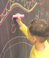 Developing handwriting skills while coloring on a chalkboard