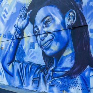 Within the mural, the word Unity next to a young woman wearing a baseball cap
