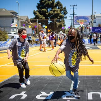 Kids play on the new multi-sport court with a yellow basketball