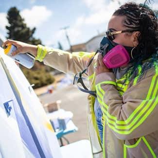 Volunteer spray paints a basketball backboard