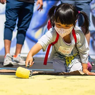 A little girl paints the asphalt with a rolling brush